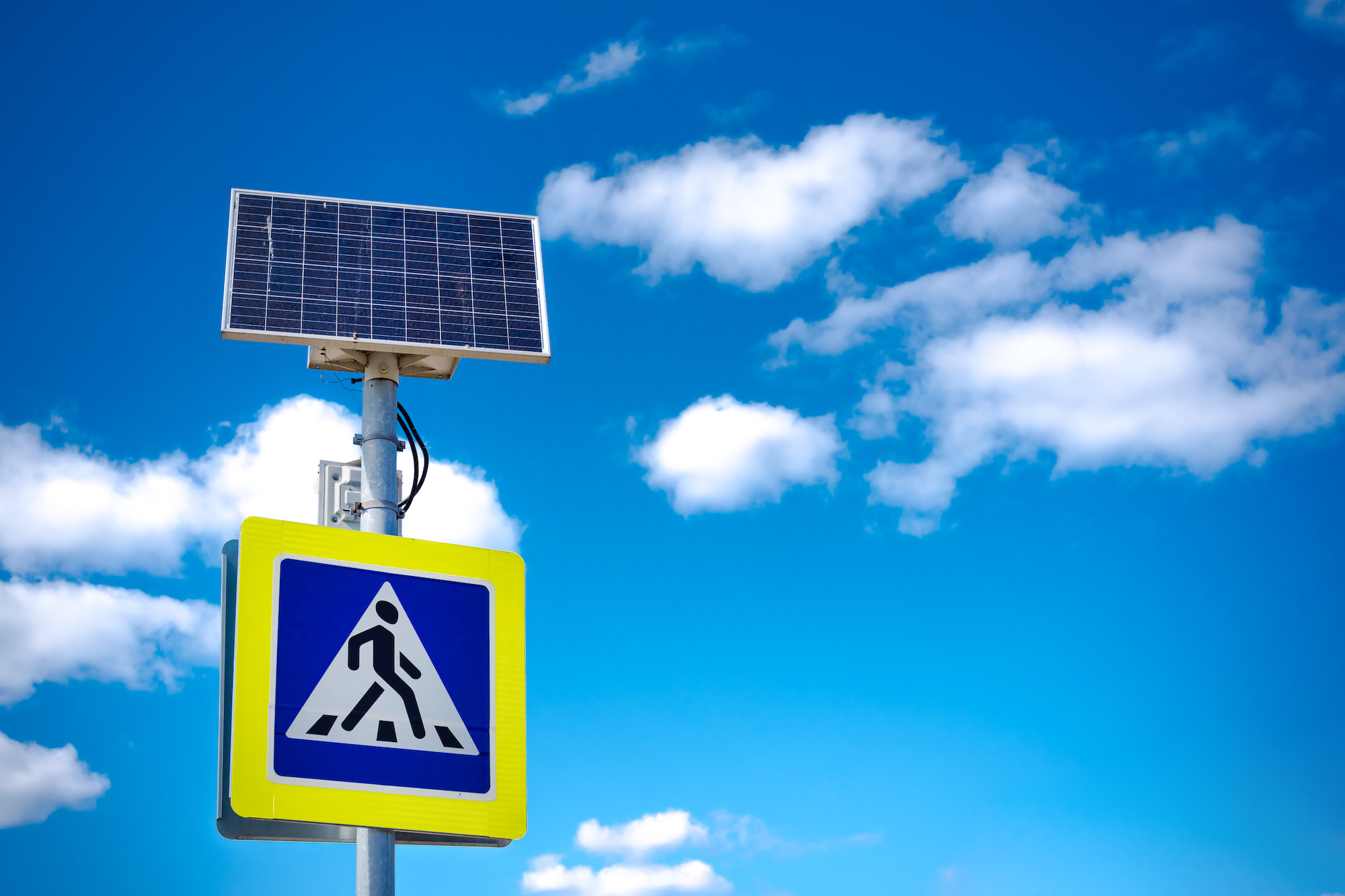 Bright blue and yellow pedestrian crosswalk sign with traffic warning. Powered by solar energy with its own solar panel
